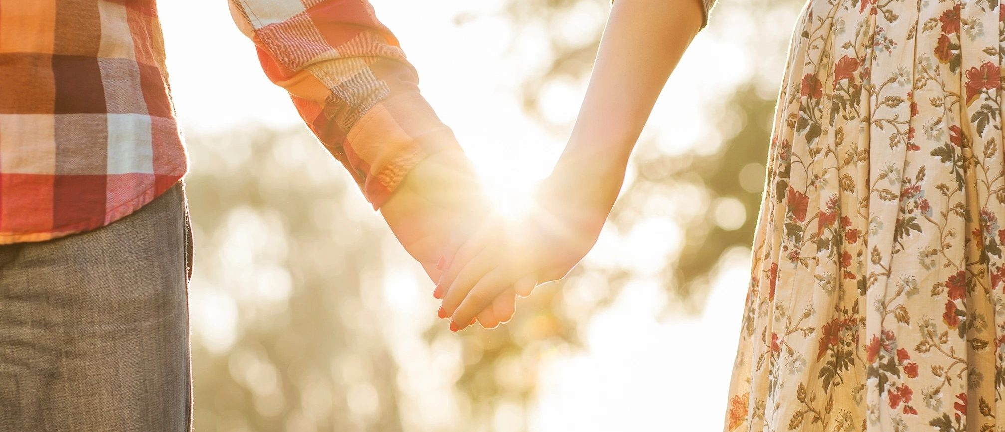 Two people holding hands. Where their hands meet, the sun shines.