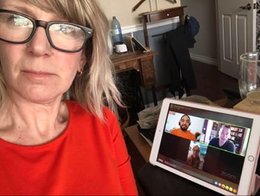 A woman taking a selfie. On the background is a virtual meeting on an iPad.
