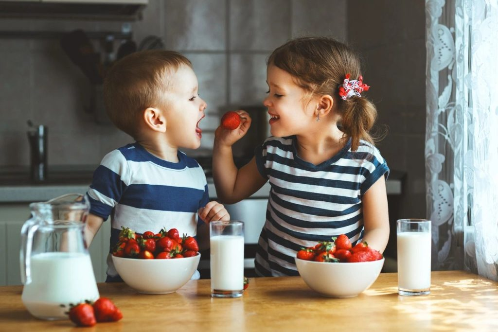 Two kids eating strawberries. There are bowls of strawberries on the table and glasses of milk.